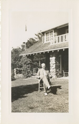 Edwin Grant Conklin seated on a chair on a lawn