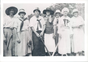 Black and white photo of seven men wearing dresses, with softball gear