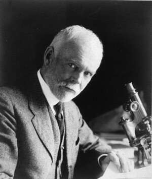 E.B. Wilson portrait with microscope looking at camera