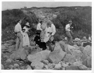 TH Morgan, EB Wilson and others on rocky beach having a picnic. Morgan in center, Wilson on right with teacup