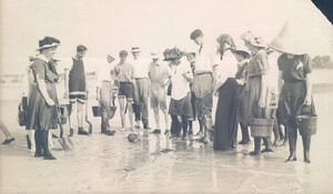 Black and white photo of the invertebrate class on a collection trip standing on the beach looking at a little animal