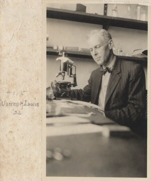 Lewis is seated at a table in front of a microscope, looking down at a paper. There are several pieces of paper and other items on the table, and there are shelves holding various boxes and glass containers on the far wall. He is wearing a pinstriped suit