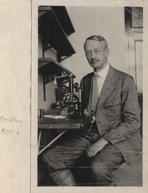 Conklin is seated at a collapsible desk in front of a microscope. He is turned toward the camera. There are shelves on the wall above the desk, and a doorway behind him to his left