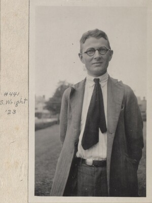 S. Wright is standing in front of a field, with his hands folded behind him