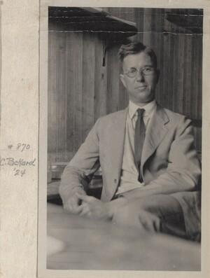 Packard sitting at his desk, facing the camera