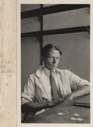 H. Keffer Hartline sitting in a chair wearing a lab coat. In front of him on a desk is a folder and few glass slides