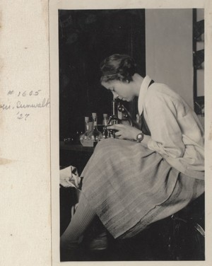 Sumwalt sitting at a lab bench while looking into a microscope