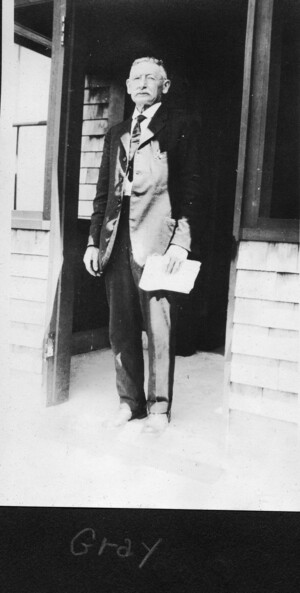 Gray standing in a doorway with some papers in his left hand