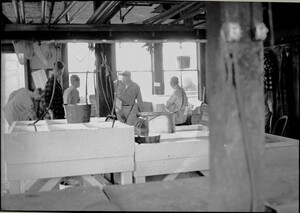 Five men sitting or standing near windows of MBL Supply House with tanks in foreground