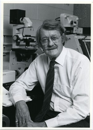 John P. Trinkaus wearing a long-sleeved white shirt, striped tie, and glasses, seated in front of a microscope