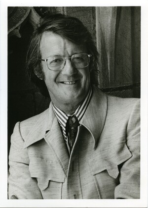 John P. Trinkaus is wearing a a striped shirt, light colored jacket, paisley tie, and glasses. Trinkaus is standing in front of a stone wall, looking at the camera and smiling